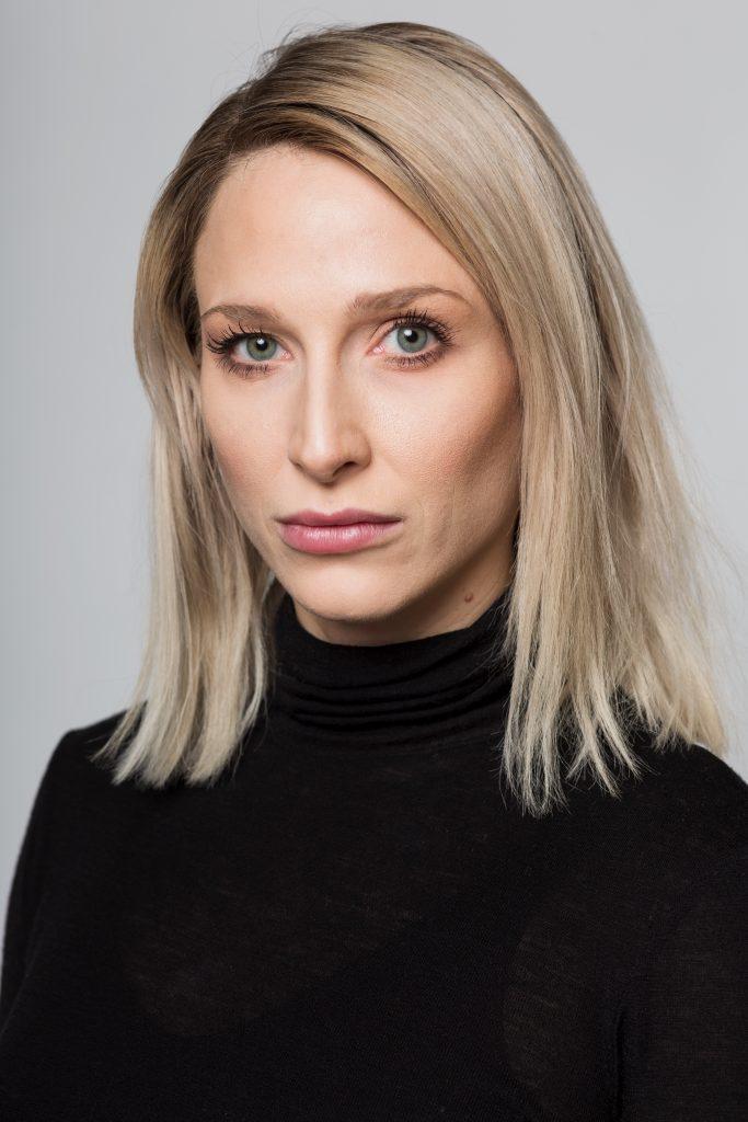 Porträt Anna-Eva Köck; eine Frau mit blonden schulterlangen Haaren blickt intensiv in die Kamera