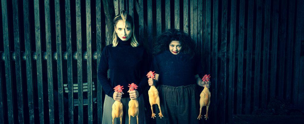 Sujet Max und Moritz, eine blonde dünne große Frau und eine kleine dicke Frau mit krausen dunklen Haaren stehen vor einem Zaun und halten vier Plastikhühner in den Händen