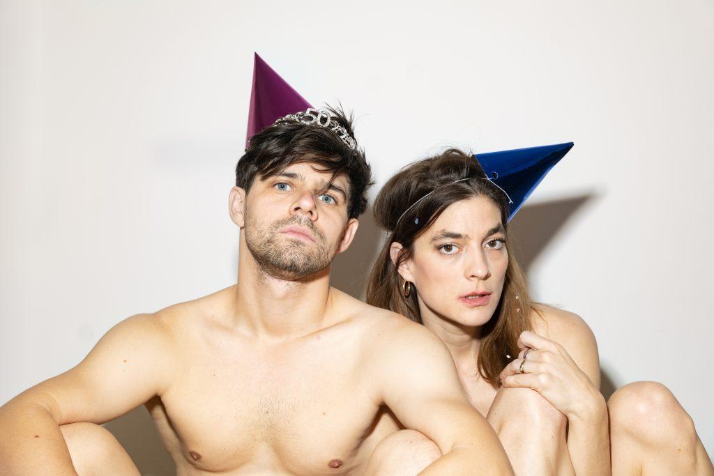 Sujet Rozznjogd, ein Mann und eine Frau sitzen nackt vor einer weißen Wand; sie tragen bunte Partyhüte