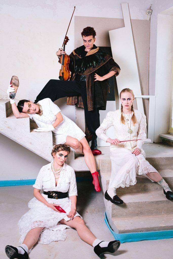 Sujet Königstöchter drei weiß gekleidete Frauen sitzen auf einer Treppe, eine schwarz gekleidete Frau hält eine Geige in der Hand